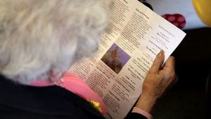 Lady reading a paper copy of The Mill newsletter