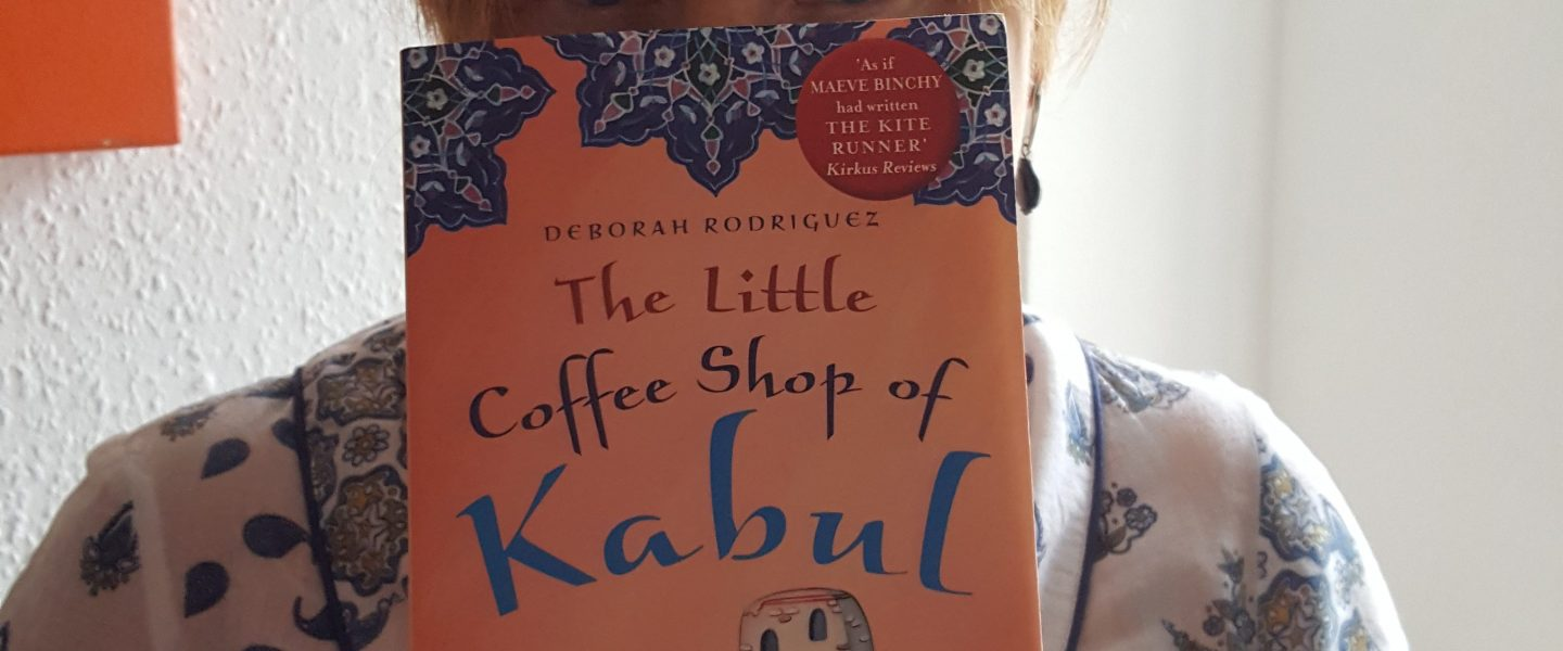Helen B holding a copy of The Little Coffee Shop of Kabul