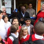 Mr Mensah opening The Mill surrounded by school children, Mill volunteers and local councillors