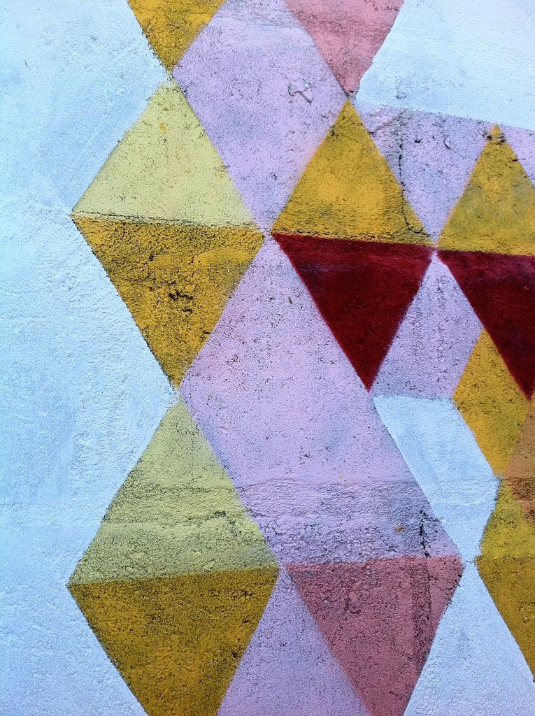 Close up of abstract wall mural, geometic gold, pink and light blue diamonds and triangles design
